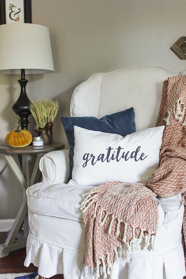 Gratitude pillow on wingback chair.