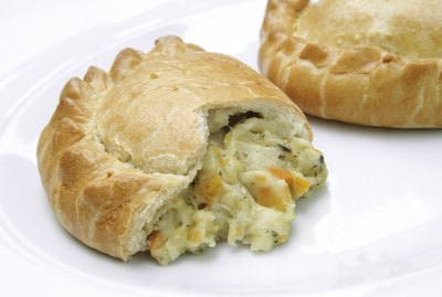 two traditional cheese and onion English pasties on white