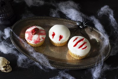 Three cupcakes decorated with zombie brain, vampire bite & monster claw