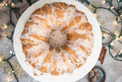 Eggnog bundt cake with glaze on a cake stand with Christmas lights around cake