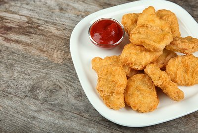 Plate with tasty chicken nuggets and sauce on table