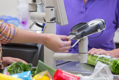 Close Up Of Woman Paying For Shopping At Supermarket Checkout
