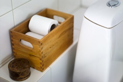 Toilet paper in crate on bathroom shelf