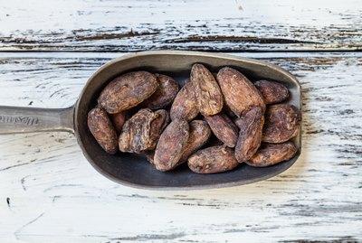 Meatl shovel of raw cocoa beans
