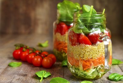 Salad with quinoa and vegetables in a mason jar.