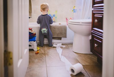 Baby playing with toilet paper in bathroom