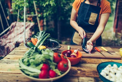 Young woman cutting vegetables outdoor