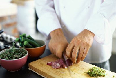 mid section view of a chef chopping onions in the kitchen