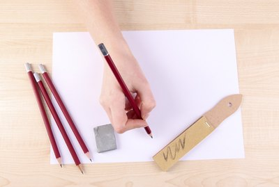 Hand holding pencil with art materials on wooden background