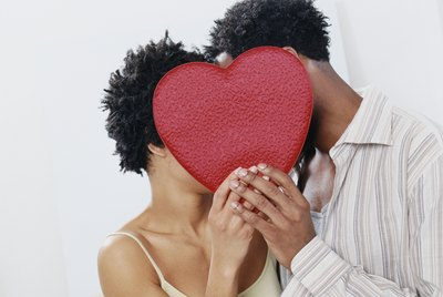 Couple Hiding Face to Face Behind a Red Heart Shape