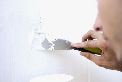 Close-up of a man applying filler to a wall with a putty knife