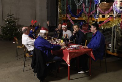 Group of workers sitting at christmas table in warehouse