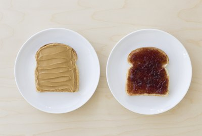 Slices of bread on plates with peanut butter and jelly