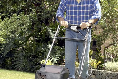 A man wearing ear protection pushes a lawn mower across the grass toward the viewer.