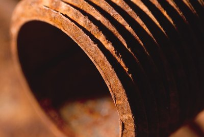 a close-up of a rusted steel pipe lying on other rusted steel pipes