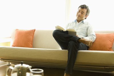 Hispanic man reading on sofa