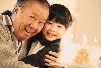 Senior man hugging grandson with birthday cake