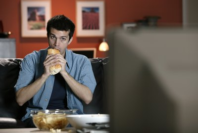 Man eating sandwich and watching television