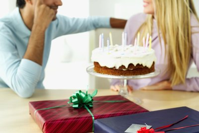 Young couple sitting beside a birthday cake and gifts