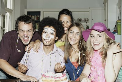 Man with icing on his face posing with friends