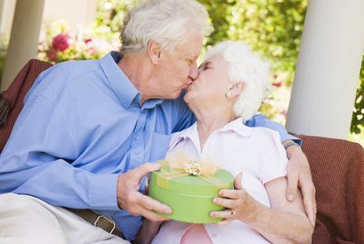 Husband giving wife gift on patio and kissing her
