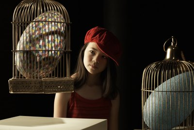 Girl (10-11) looking at giant colorful egg in cage