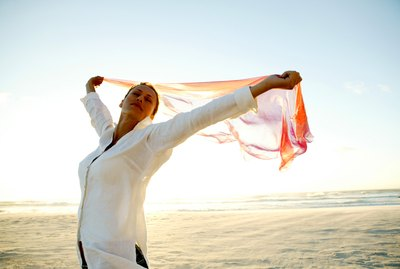 Woman on the beach with windblown scarf