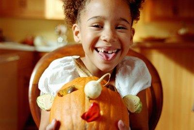 Girl (6-8) holding decorated pumpkin, smiling, portrait
