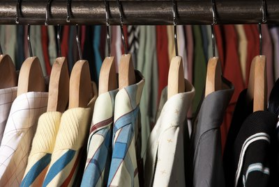 Shirts on wooden hangers on clothes rack