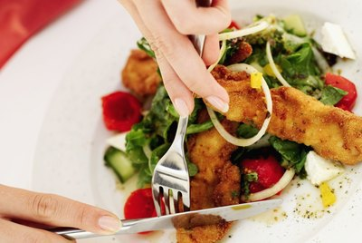 Close-up of a woman's hands slicing a piece of fried fish with fork and knife