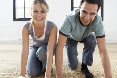 Couple unrolling carpet, smiling, portrait