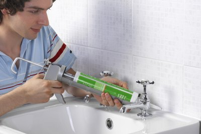 Man using caulking gun on sink