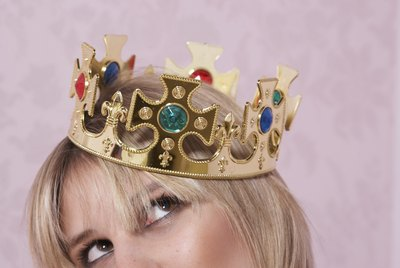 Young woman wearing crown, looking up, close-up