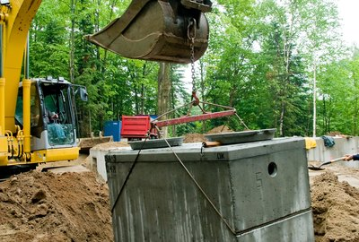 Installing septic tank with excavator at construction site