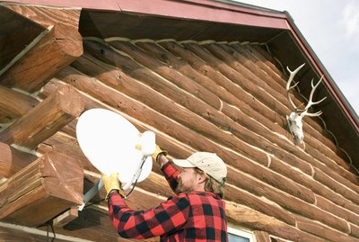Man installing satellite dish on house