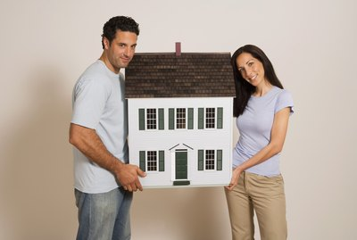 Woman and man holding miniature house