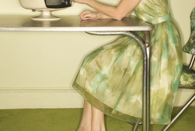 Side view of Caucasian mid-adult woman wearing green vintage dress sitting at 50' || chr(39) || 's retro dinette set turning old televsion knob.