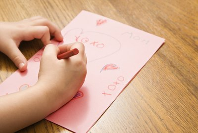 Caucasian female child hands drawing on paper with crayons.