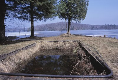 Abandoned swimming pool on shore by lake