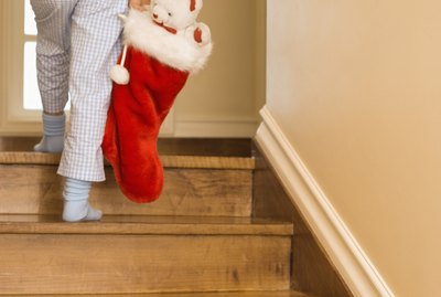 Child walking up stairs with Christmas stocking