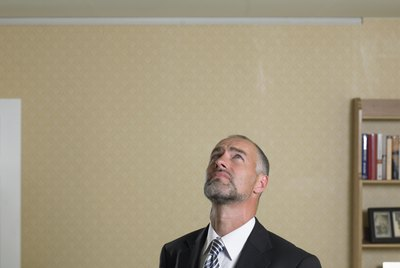 Mature man in suit with clipboard looking up at crack in ceiling