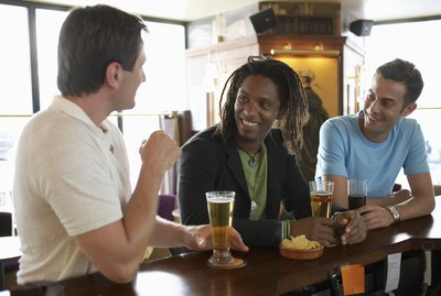 """Three men drinking at bar, smiling"""