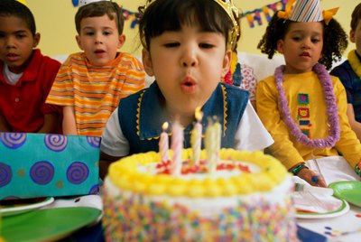 Girl (5-7) blowing out birthday candles