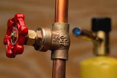 Shut-off valve on copper pipe; blowtorch in background