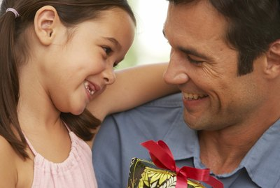 Girl (5-7) embracing father, close-up