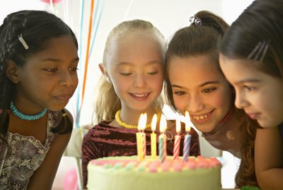 Four Young Girls Sit Around a Birthday Cake at a Party, the Birthday Girl About to Blow the Candles Out