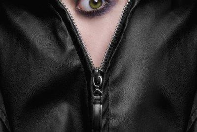 frightened green eyed girl hiding behind the zipper