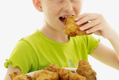 portrait of a girl (6-9) eating fried chicken