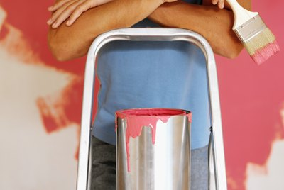 Close-up of a young man standing on a ladder with a paint bucket and brush