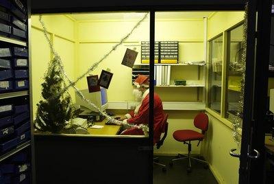 Teenage boy(16-17 years) dressed as santa using computer in office, side view